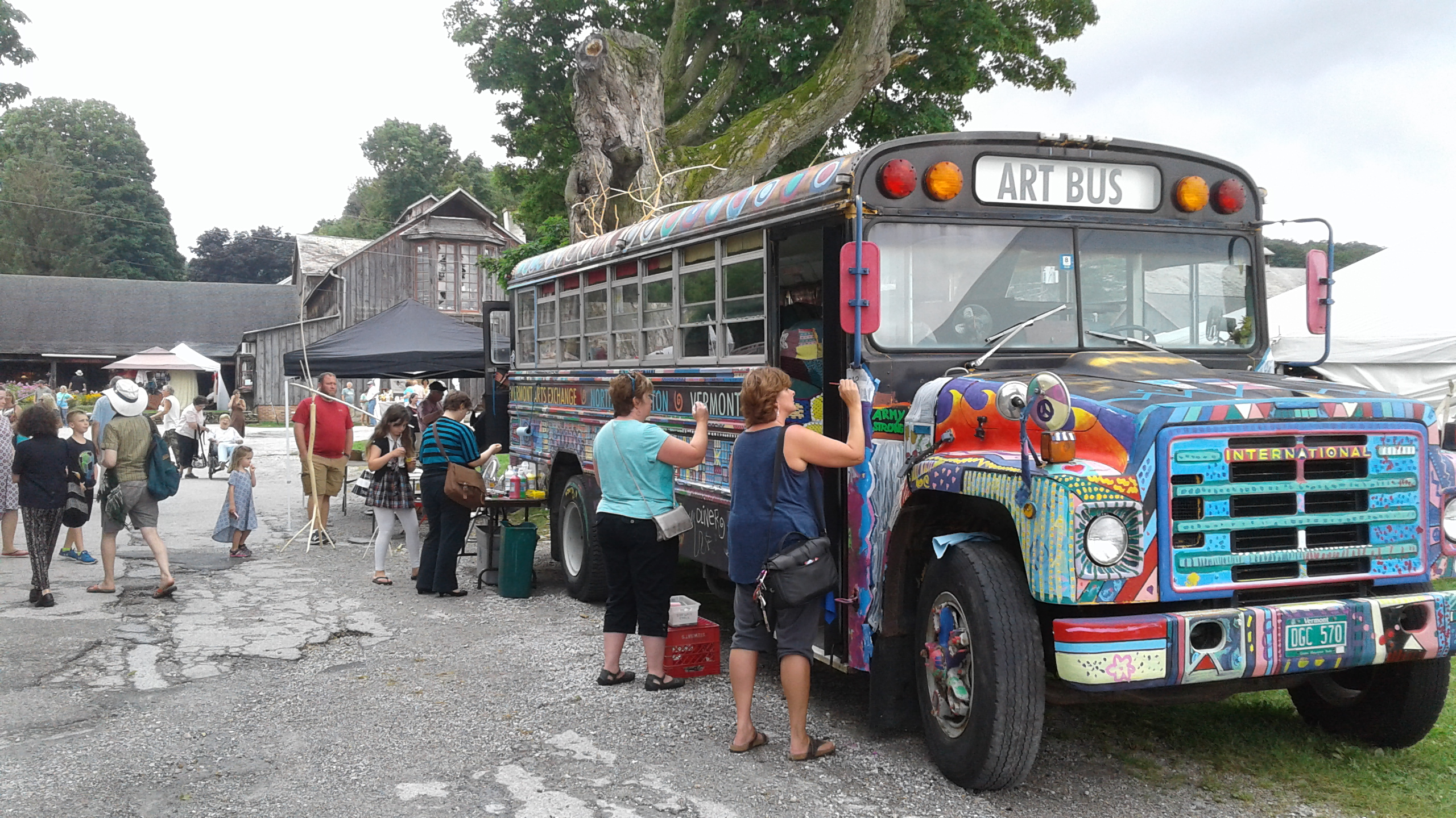 individuals painting an art bus
